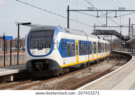 Train stopping in train station in The Netherlands - stock photo