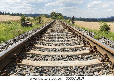 Train tracks going into the horizon with blue sky above - stock photo