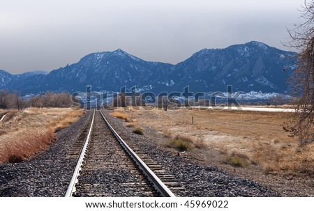 Train tracks in sunlight lead off into the distance towards mountains and a brewing storm on the Colorado prairie near Boulder through a golden field of winter grasses - stock photo