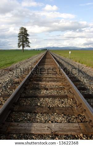 Train tracks through a farm field. - stock photo