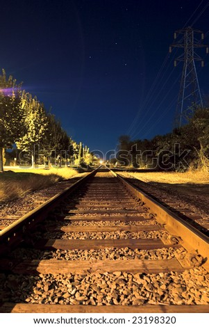 Train tracks under night blue sky - stock photo
