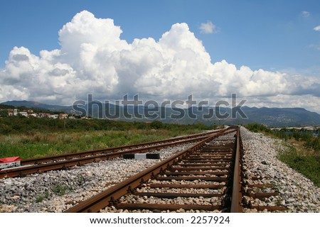 train tracks with clouds in the background