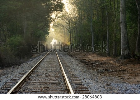 Train tracks with light at end of tunnel - stock photo