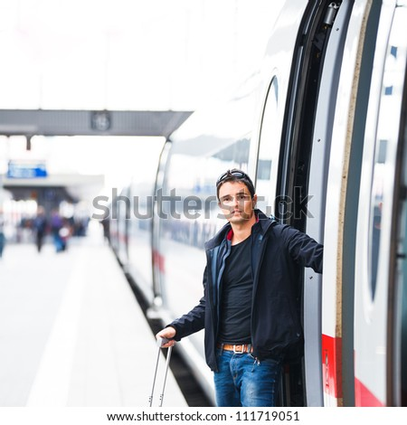 Train travel - Handsome young man taking a train - stock photo