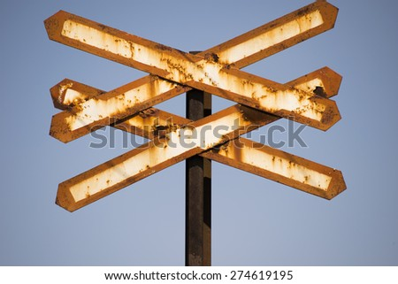 Train warning sign having the shape of two X letters. Blue background. - stock photo