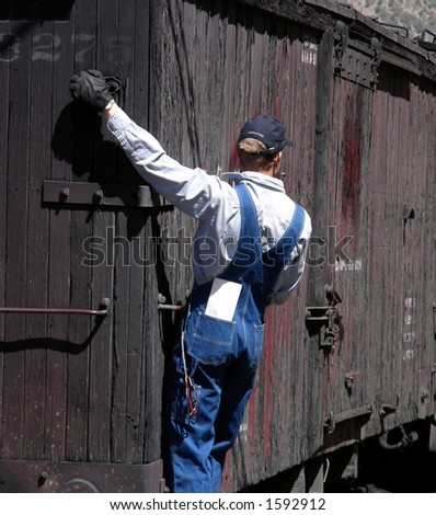 Train worker hanging on the back of a freight car