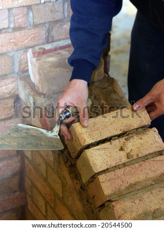 Trainee bricklayer positioning brick on wall support - stock photo