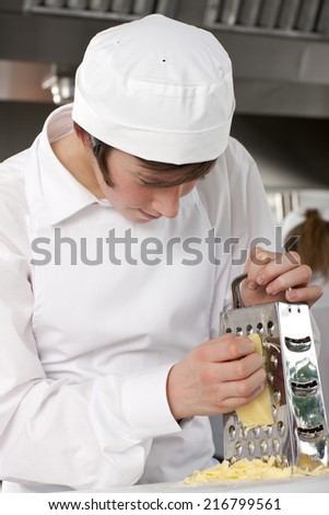 Trainee chef grating cheese in commercial kitchen