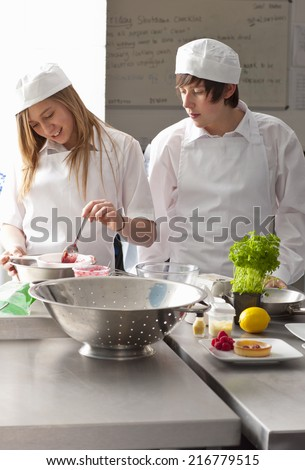 Trainee chefs working together in commercial kitchen - stock photo