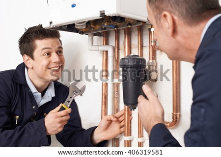 Trainee Plumber Working On Central Heating Boiler - stock photo