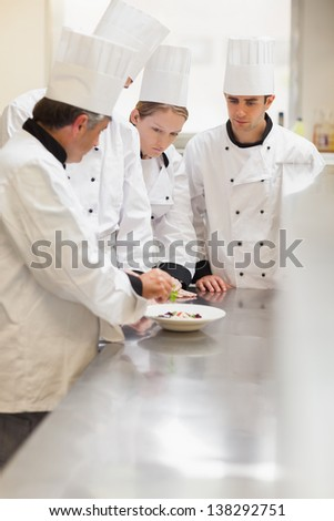 Trainees listening to the head chef in the kitchen at culinary school - stock photo