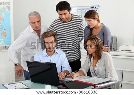 Trainees looking at a laptop - stock photo