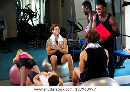 Trainees performing aerobics with swiss ball before their trainer. - stock photo