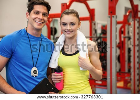 Trainer and woman discussing workout plan at the gym