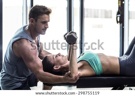 Trainer assisting a muscular woman lifting dumbbells - stock photo