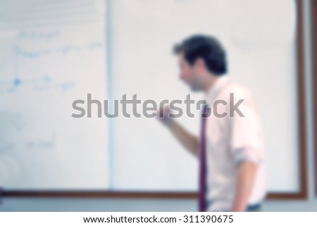Trainer blur in front of whiteboard at the classroom instructs new business model - stock photo