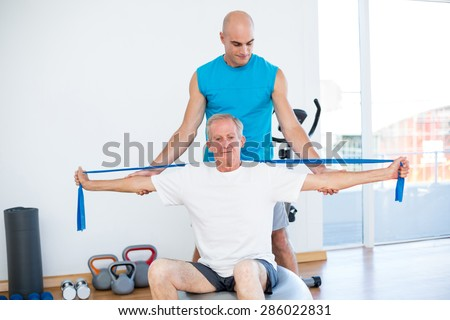 Trainer examining his patient back in fitness studio - stock photo