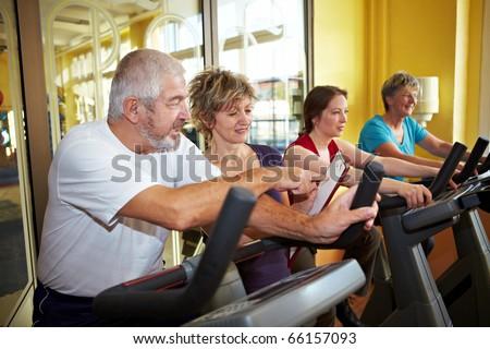 Trainer explaining coaching plan to senior in gym - stock photo
