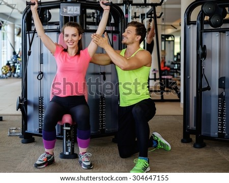 Trainer explaining how to use training machine in a gym - stock photo