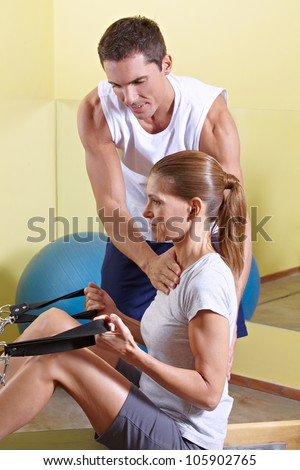 Trainer giving advice to woman in fitness centerat rowing machine - stock photo