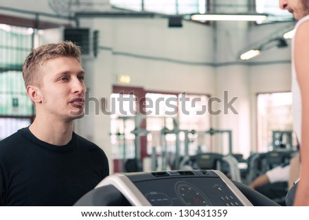 Trainer giving instructions training in the gym. - stock photo
