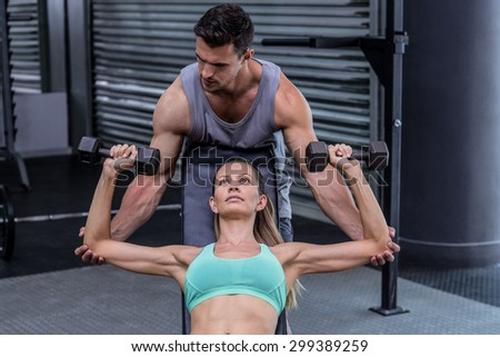 Trainer helping a muscular woman lifting dumbbells - stock photo
