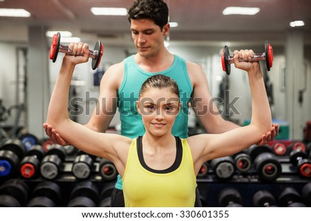 Trainer helping client work out at the gym