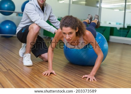Trainer helping his client doing push up on exercise ball at the gym - stock photo