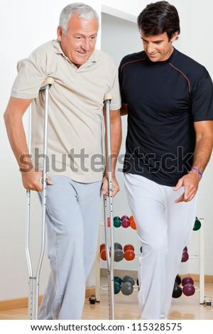Trainer helping senior man with crutches to walk - stock photo