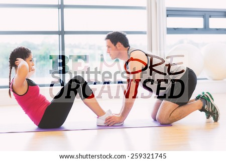Trainer helping woman do abdominal crunches in gym against be more organised - stock photo