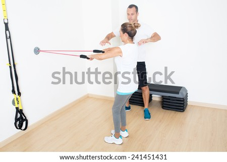 Trainer helps elderly woman with fitness exercise on skipping rope - stock photo