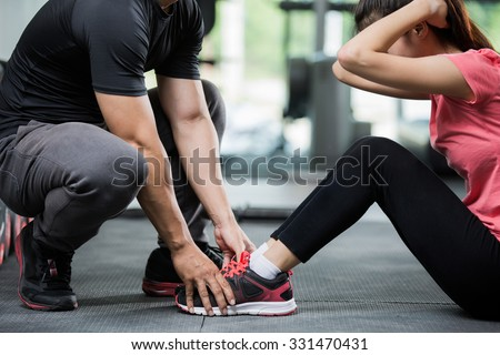 Trainer holding a woman in the leg exercise by Sit-up. - stock photo