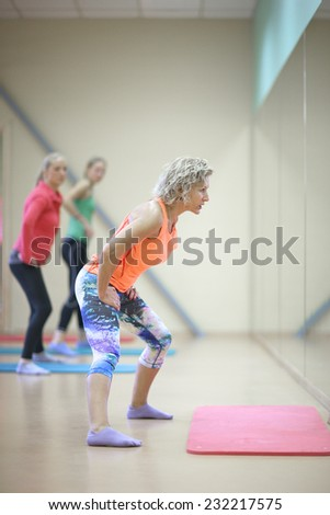 Trainer in front of the mirror showing fitness exercises - stock photo
