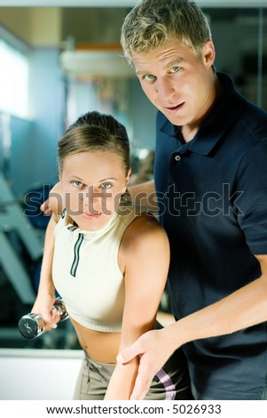 Trainer instructing a beautiful woman in the gym on how to properly exercise - stock photo