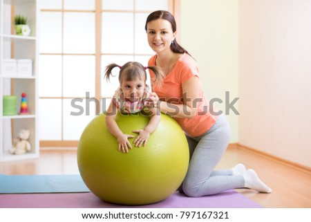 Trainer instructor with kid doing fitness on ball