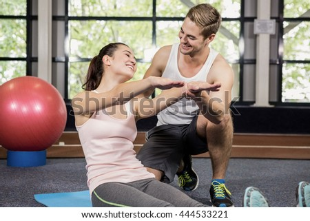 Trainer motivating a woman while doing crunches at gym - stock photo