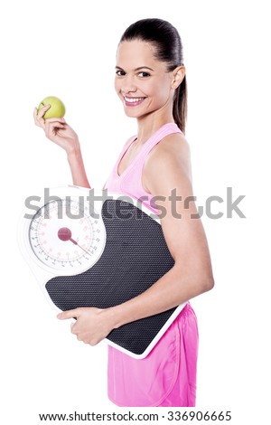 Trainer posing with apple and weigh scale - stock photo