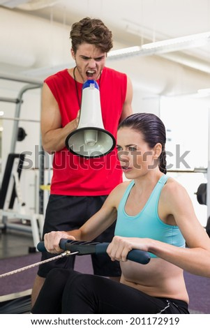 Trainer shouting at client through megaphone at the gym