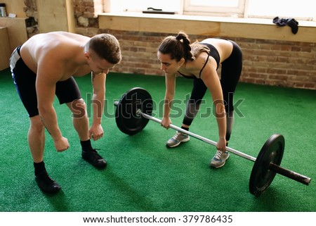 Trainer spotting a woman while she's exercising with weight - stock photo