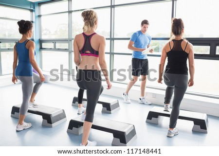 Trainer teaching his aerobic class in gym - stock photo