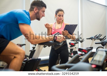 Trainer timing man on exercise bike at the gym - stock photo