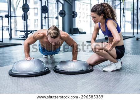 Trainer watching muscular man doing bosu ball push ups - stock photo