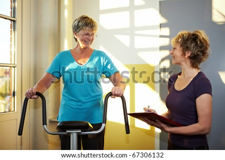 Trainer with eldery woman on treadmill in gym - stock photo