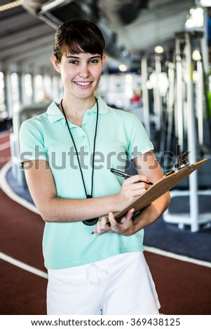 trainer with notes smiling at camera