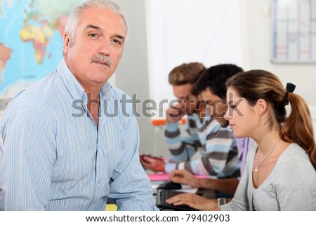 Trainer with pupils in classroom - stock photo
