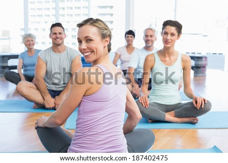 Trainer with sporty people sitting on exercise mats at a bright fitness studio - stock photo