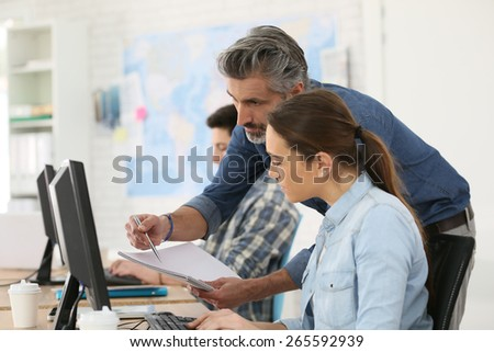Trainer with student working on desktop computer - stock photo