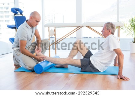 Trainer working with man on exercise mat in fitness studio