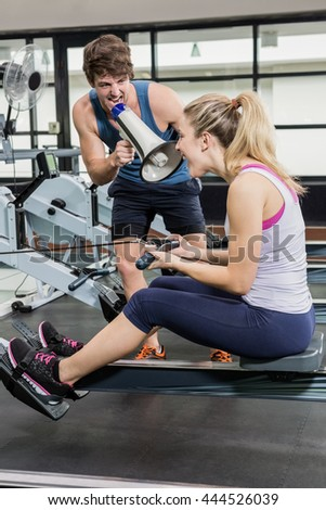 Trainer yelling through a megaphone while woman on rowing machine at gym