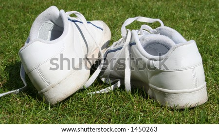 trainers, sneakers abandoned on grass background - stock photo